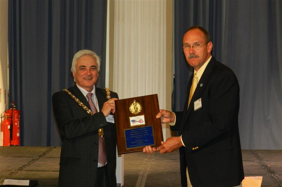 Twinning Committee chairman presents official plaque during a 2012 exchange in Cheltenham UK.